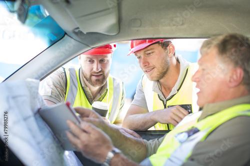 Bauarbeiter diskutieren Bauplan im Auto\