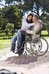 Frau umarmt Mann im Rollstuhl
