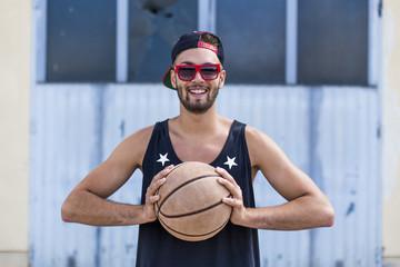 Porträt des lächelnden jungen Mannes mit Basketball, Basecap und Sonnenbrille