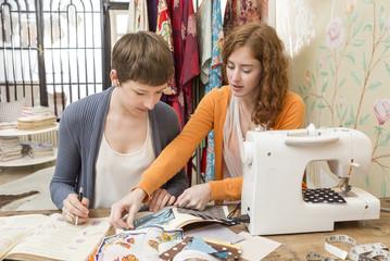 Zwei Mode-Designerinnen arbeiten zusammen in ihrem Studio