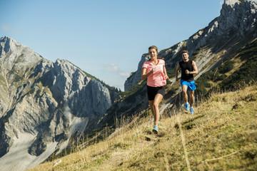 Österreich, Tirol, Tannheimertal, junges Paar joggt in den Bergen
