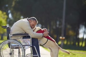 Mann im Rollstuhl umarmt Hund im Park