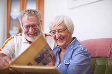 Paar schaut Fotoalbum an, zu Hause