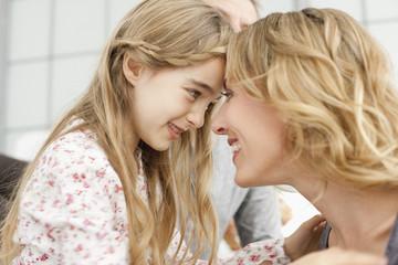 Deutschland, Leipzig, Mutter und Tochter blicken einander an, lächelnd