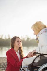 Enkelin Hand in Hand mit ihrer Großmutter im Rollstuhl