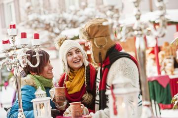Österreich, Salzburg, Mann und Frauen auf dem Weihnachtsmarkt, lächelnd