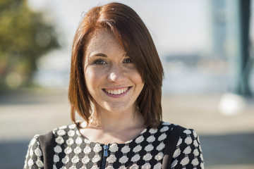 Portrait der lächelnden jungen Frau im Freien