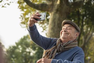Lächelnder älterer Mann macht ein Selfie