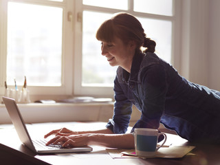 Lächelnde Frau am Schreibtisch mit Laptop