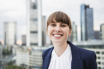 Deutschland, Hessen, Frankfurt am Main, lächelnde Geschäftsfrau vor Skyline