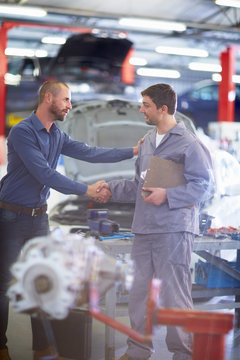 Car mechanic and client shaking hands in repair garage