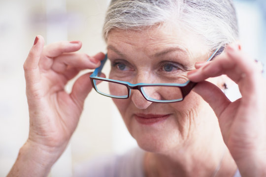 Senior woman at the optician trying on glasses