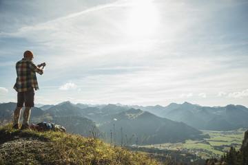 Österreich, Tirol, Tannheimer Tal, junger Mann macht Foto in Bergen