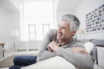 Deutschland, Bayern, München, älterer Mann sitzt auf der Couch, lächelnd
