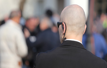 robust security guard with the headset and black glasses