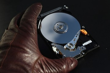 Protect your data, hand with glove over open hard disk