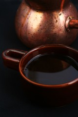 Traditional black turkish coffee in copper coffee pot