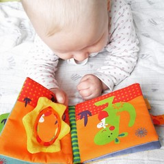 Blond baby reading book
