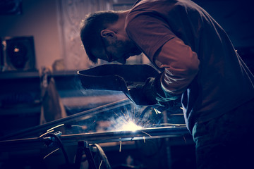 Employee at the factory welding steel using MIG MAG welder.