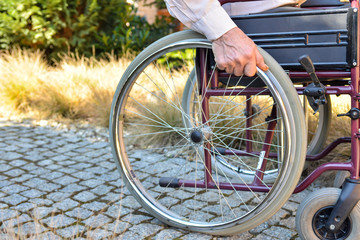 Close-up of male hand on wheel of wheelchair