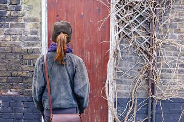 Woman standing by old rustic  door