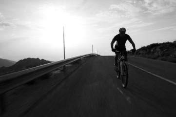 Cyclist man riding mountain on a mountain road, silhouette sunri