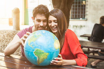 Young couple looks the world map