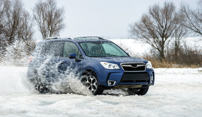 Powerful offroader car sliding by lake ice