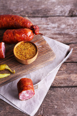 Smoked sausage on cutting board on wooden table background