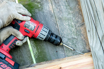 man drilling holes for wood fence repair