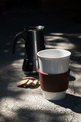Hot coffee and moka pot with biscuits