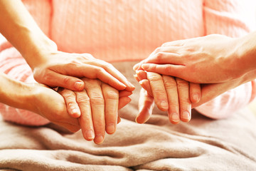 Old and young holding hands, closeup