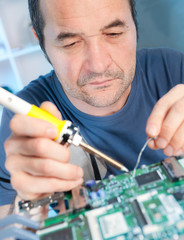 Senior tech fixes computer circuit board