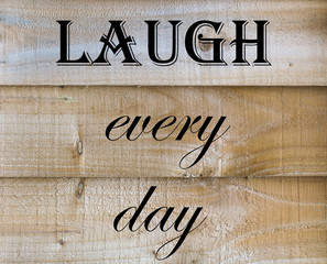 Laugh Every Day quote on a wooden background