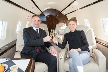 executive business team in a corporate jet drinking a glass of c