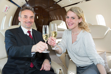 cheers clink glasses business team in a corporate jet drinking c