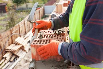 Construction mason worker bricklayer installing brick