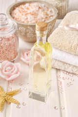 Pink spa set: bottle of rose essential oil, towels and sea salts
