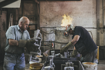 Two craftsmen preparing molds for casting in a foundry
