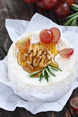 Camembert with walnuts and honey on a rustic wooden table.