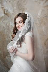 Portrait of the smiling bride with perfect make up and hairstyle