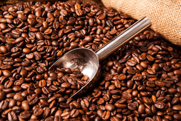 Wall Mural - roasted coffee beans with scoop in bag