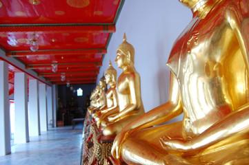 Gold buddha statues at thai monastery