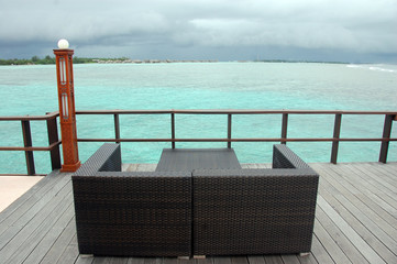 Brown couch at timber pier ocean view