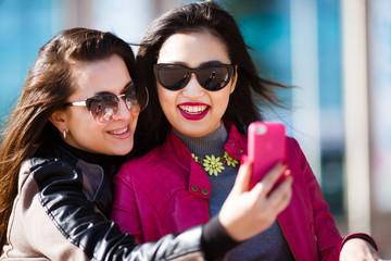 Two happy women making selfie photo