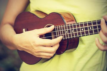 Woman playing ukulele, vintage style.