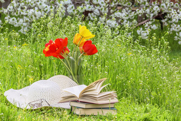 Bouquet of tulips,  books, a hat on the grass