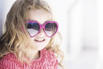 Happy little girl wearing heart shaped sunglasses