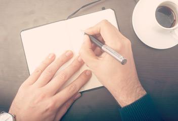 Man writing notes at the cafe