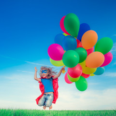 Superhero with toy balloons in spring field